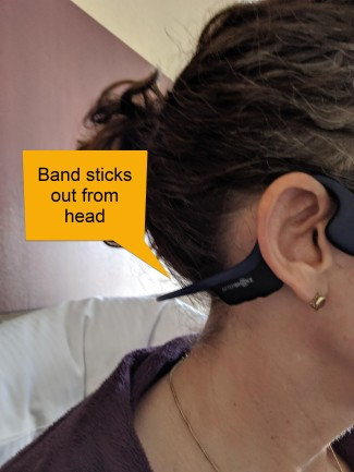 Shows headphone band sticking out behind neck